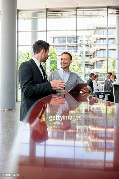 Two men in discussion at reception desk