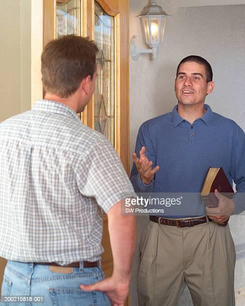 Two men in doorway, one man holding Bible