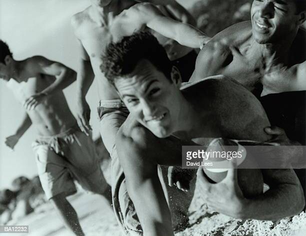 Two men in football tackle on beach, close-up (B&W)
