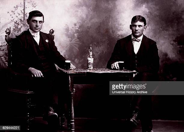Two Men in Formal Attire Sitting at Table Drinking Beer circa 1900