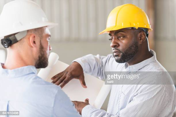 Two men in hardhats discussing blueprints