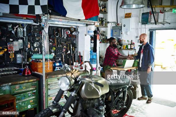 Two men in motorcycle workshop.