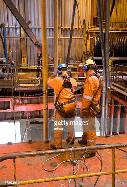Two men in orange working on an oil rig