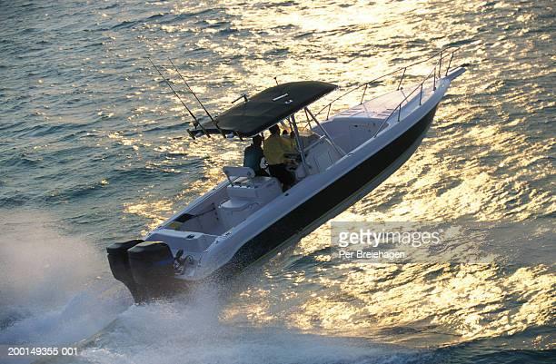 Two men in powerboat going deep sea fishing, rear view