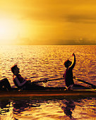 Two men in rowing boat, one raising arm, sunrise