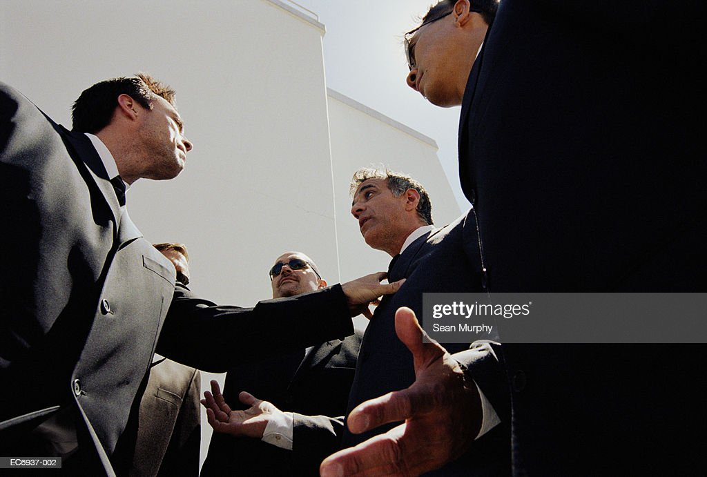 Two men in suits arguing,  surrounded by bodyguards : Foto stock