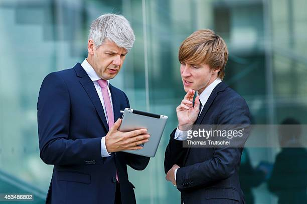 Two men in suits discuss bent over an ipad on August 07 2014 in Berlin Germany