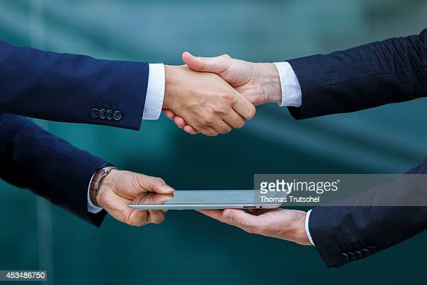 Two men in suits shaking hands with iPad on August 07 2014 in Berlin Germany