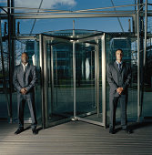 Two men in suits, standing either side of revolving door, portrait