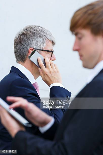 Two men in suits with iPad and mobile phone on August 07 2014 in Berlin Germany