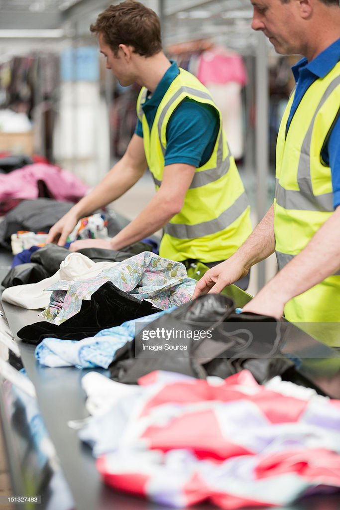 Two men in warehouse sorting clothing on conveyor belt : Stock Photo