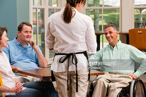 Two men in wheelchairs and a friend ordering food in a cafe