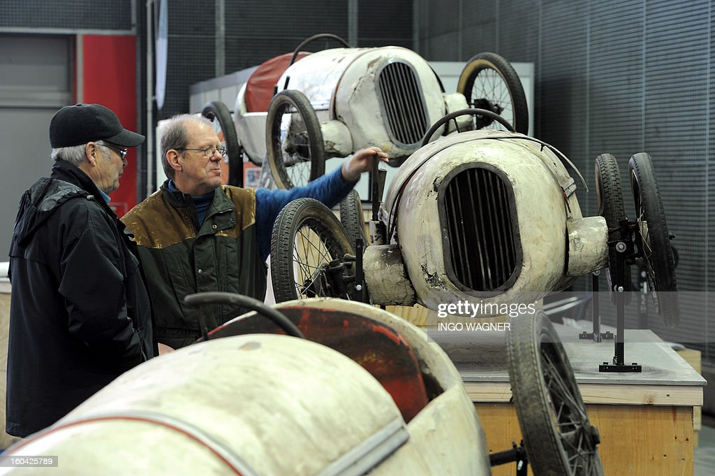 Two men inspect soap box pedal cars from 1948, originating from Hamburg's Tierpark Hagenbeck zoo, as preparations are under way for the Bremen Classic vintage car motor show on January 31, 2013 in Bremen, nothern Germany. The fair running from February 1 to 3, 2013 is themed 'Racing and Rallye: The Wild Years!'. AFP PHOTO / INGO WAGNER GERMANY OUT