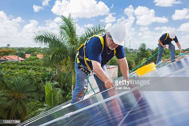 Two men installing solar panel on house roof