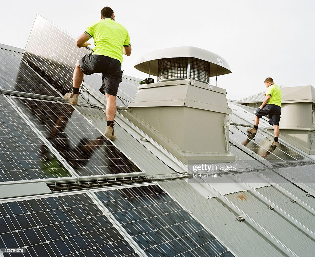 Two men installing solar panels on roof : Stock Photo