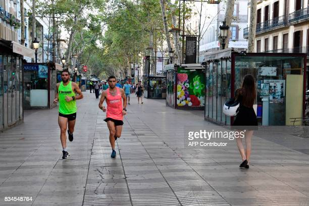Two men jog on the Rambla boulevard on August 18 a day after a van ploughed into the crowd killing 13 persons and injuring over 100 on the Rambla in...