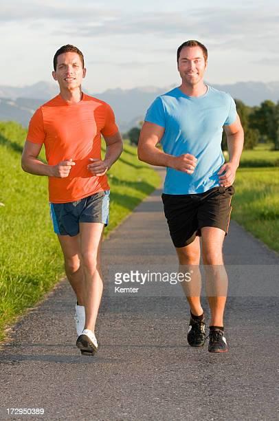 Zwei Männer Joggen auf der Straße an einem sonnigen Tag