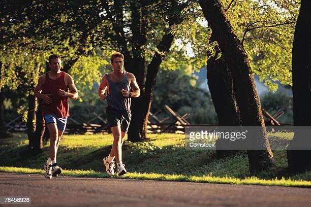 Two men jogging on suburban street