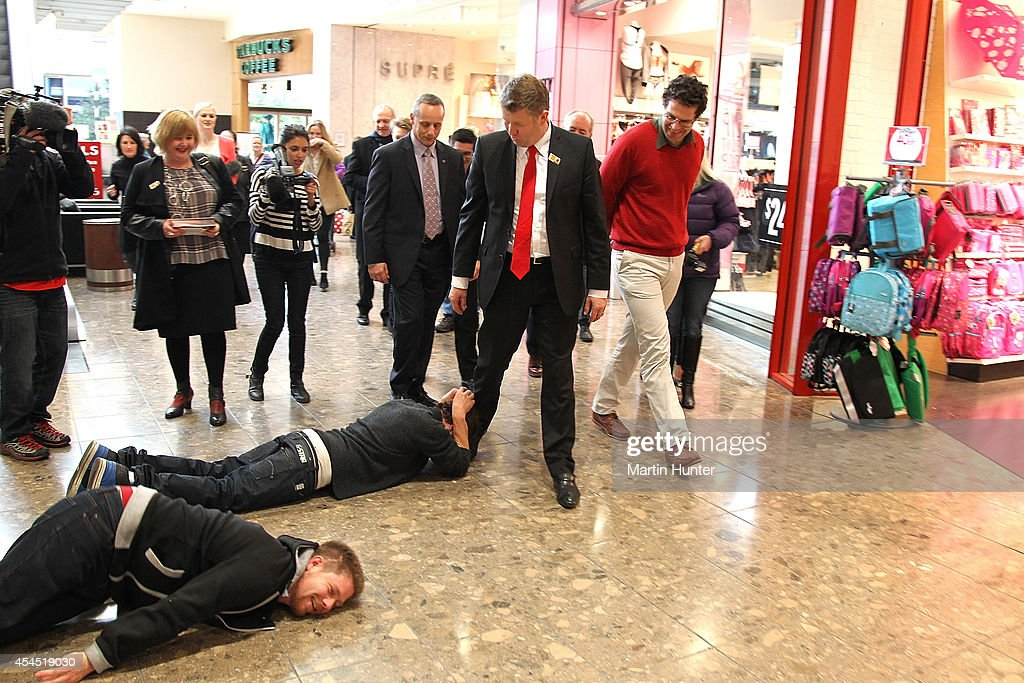 Two men jump on the floor in front of Labour Party leader <a gi-track='captionPersonalityLinkClicked' href=/galleries/search?phrase=David+Cunliffe&family=editorial&specificpeople=707125 ng-click='$event.stopPropagation()'>David Cunliffe</a> as he walks through Riccarton Mall after casting an early vote September 3, 2014 in Christchurch, New Zealand. Cunliffe cast an early vote before travelling to Auckland to campaign ahead of the September 20 election.