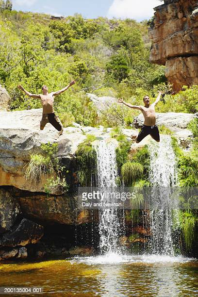 Two men jumping into rock pool, arms outstretched