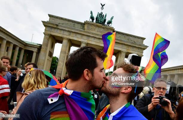 TOPSHOT Two men kiss as they attend a rally of gays and lesbians in front of the Brandenburg Gate in Berlin on June 30 2017 The German parliament...