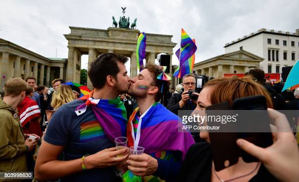 Two men kiss as they attend a rally of gays and lesbians in front of the Brandenburg Gate in Berlin on June 30 2017 The German parliament legalised...