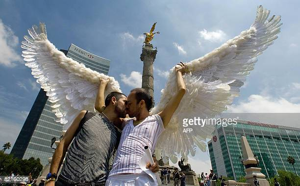 Two men kiss each other while attending the first international march against stigma discrimination and homophobia in Mexico City on 2 August 2008 in...