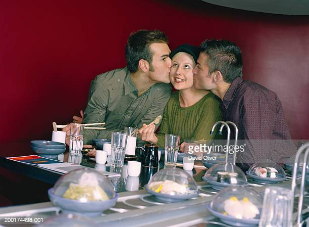 Two men kissing woman on either cheek in sushi restaurant
