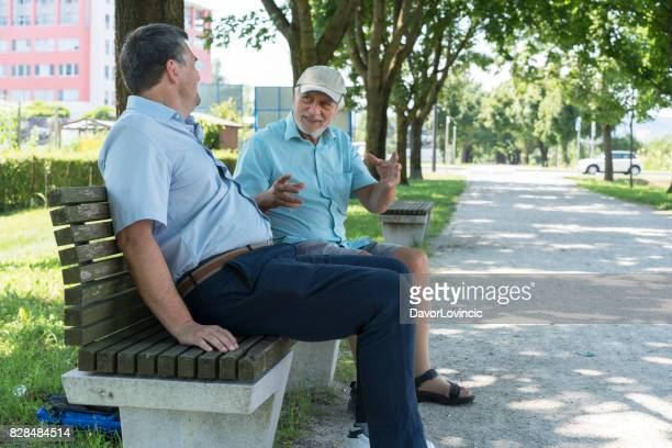 Two men laughing while sitting on bench on The Trail of Remembrance and Comradeship in Ljubljana, Slovenia