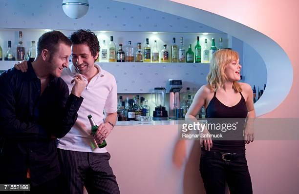 Two men leaning against a bar near a beautiful young woman