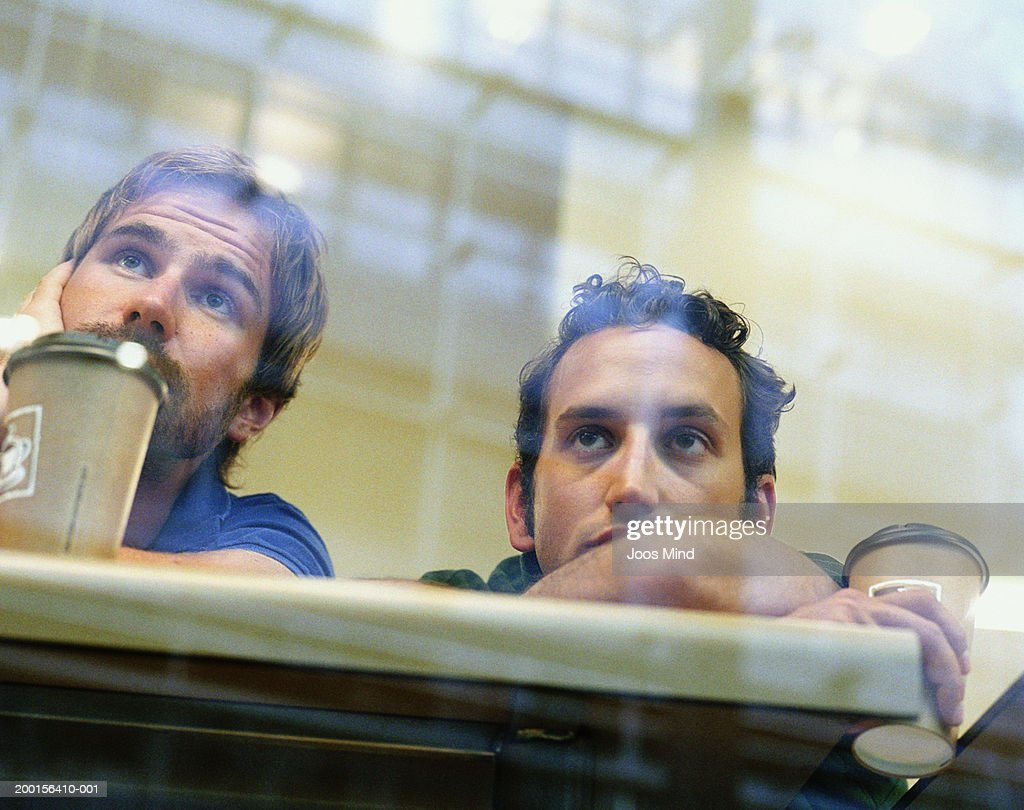 Two men leaning on cafe bench, view through window, low angle view : Stock Photo