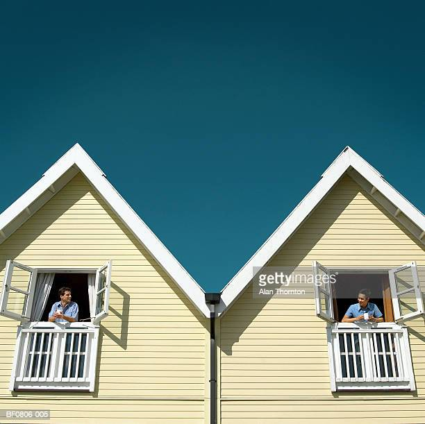 Two men leaning out of adjoining chalet windows (digital composite)