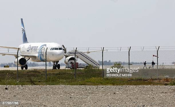 Two men leave an EgyptAir Airbus A320 parked at the tarmac of Larnaca airport after being hijacked and diverted to Cyprus on March 29 2016 / AFP /...