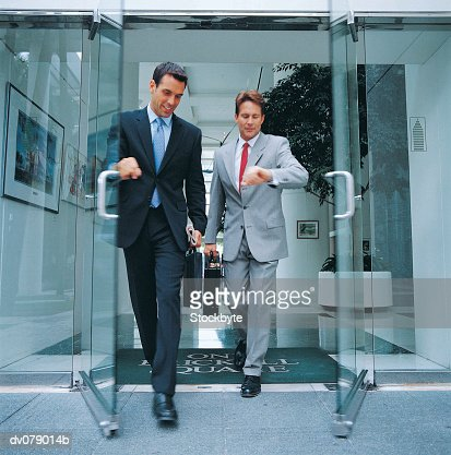 Two men leaving building together : Stock Photo