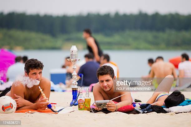 Two men lie on the beach and smoke a shisha at Silbersee Lake in Haltern am See western Germany on July 27 2013 as temperatures in Germany topped the...