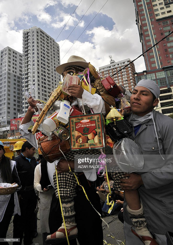 Two men lift a man dressed as Aymara 'God of Abundance', Ekeko, during the 'Alasitas' -'buy be' in Aymara native language- festivity in La Paz on January 24, 2013. In the pagan-religious festivity, people buy miniature goods, which according to their belief, Ekeko will become true. AFP PHOTO/Aizar Raldes