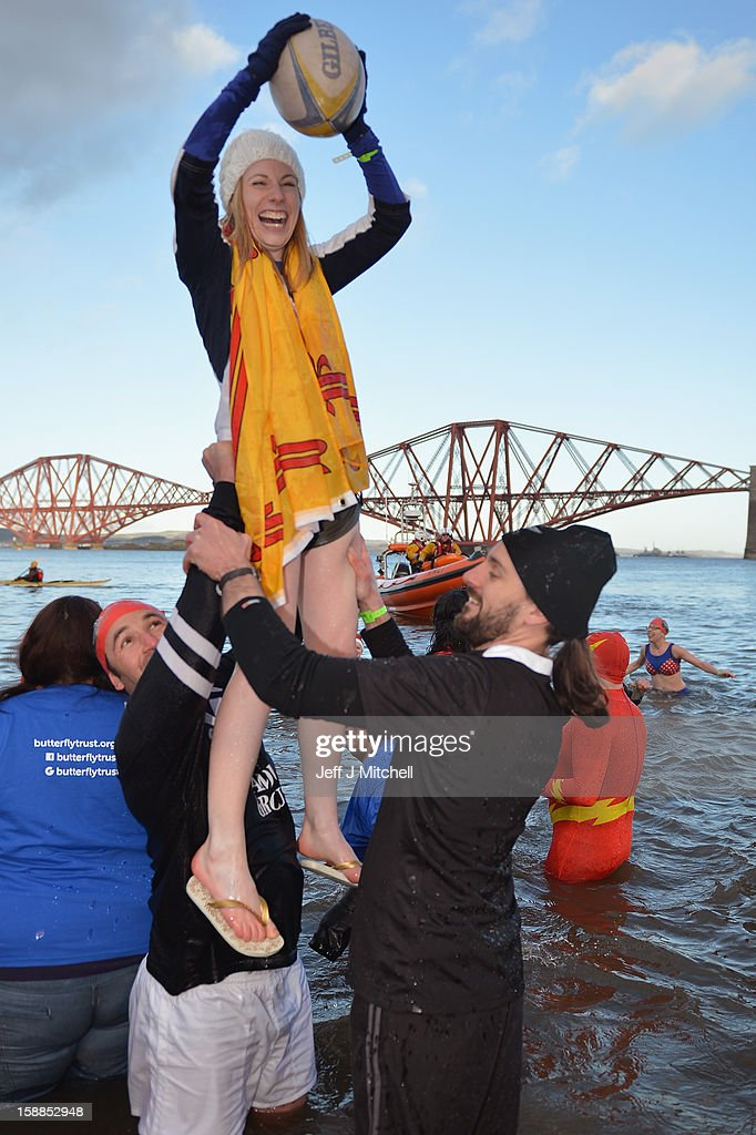 Two men lift a woman holding a rugby ball as they joined over 1,000 New Year swimmers, many in costume, braved freezing conditions in the River Forth in front of the Forth Rail Bridge during the annual Loony Dook Swim on January 1, 2013 in South Queensferry, Scotland. Thousands of people gathered last night to see in the New Year at Hogmanay celebrations in towns and cities across Scotland.