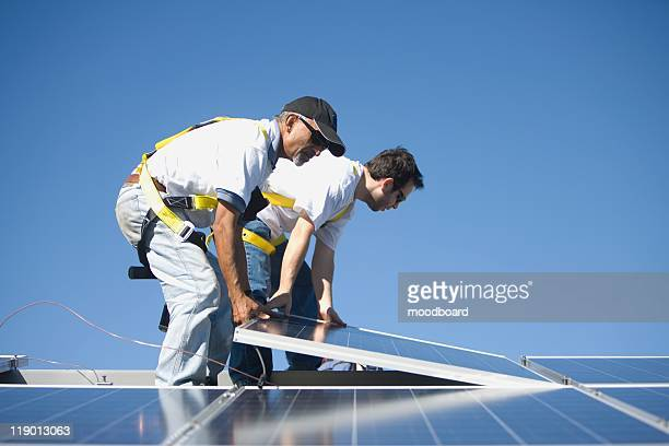 Two men lifting a solar panel