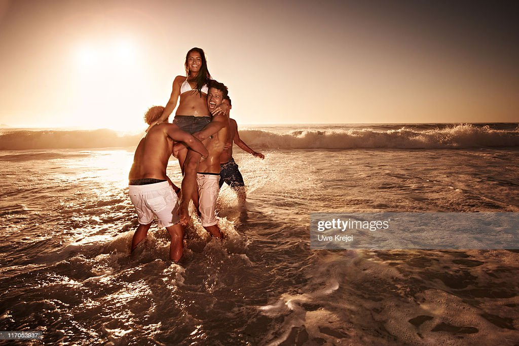 Two men lifting woman in sea : Stock Photo