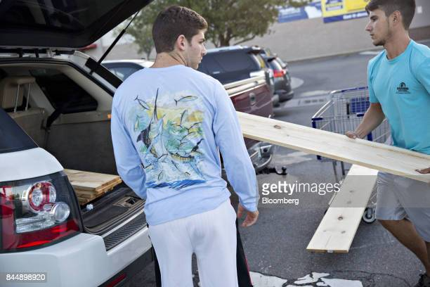 Two men load wooden boards into a vehicle outside a Lowe's Cos store ahead of Hurricane Irma in Tampa Florida US on Saturday Sept 9 2017...