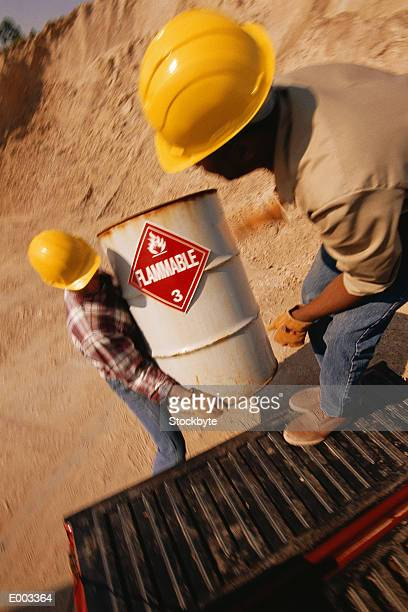 Two men loading barrel with flammable sign