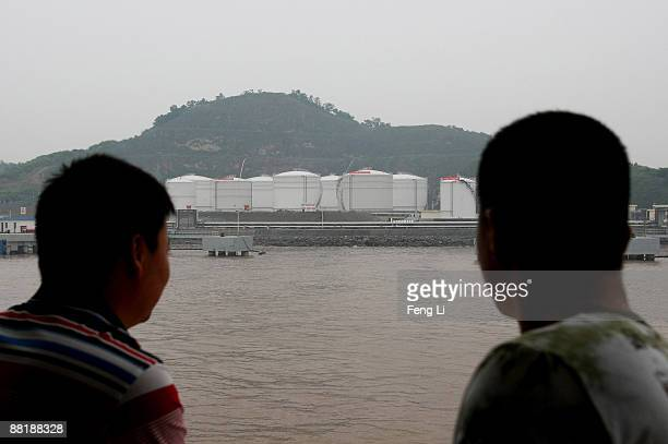 Two men look across at the oil reserve base on the seashore June 3 2009 in Ningbo of Zhejiang Province China China started to build national oil...