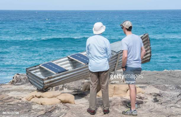 Two men look and listen to 'Les St Hill and the Tin Canoe' by John Blay Amanda Stuart and Jane Ulman at Sculpture By The Sea on October 18 2017 in...