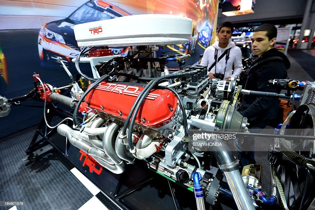 Two men look at a Toyota Racing Development engine built for their Nascar race car at a public preview of the New York International Auto Show on March 29, 2013 in New York. AFP PHOTO/Stan HONDA