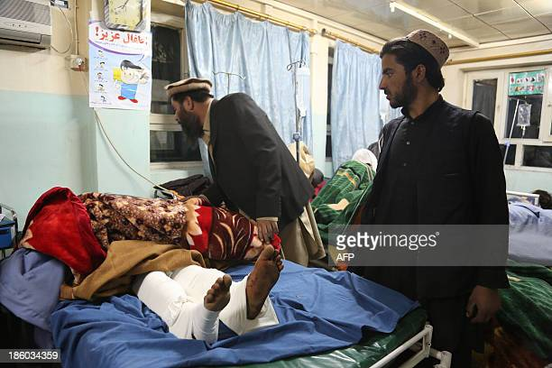 Two men look at a victim of a roadside bomb at a hospital in the Andar district of the Ghazni province on October 27 2013 A roadside bomb on October...