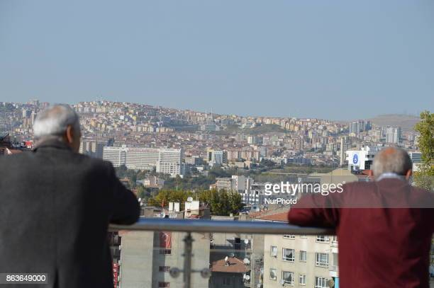 Two men look at an urban landscape of apartments and residential buildings in the historic Ulus district of Ankara Turkey on October 20 2017