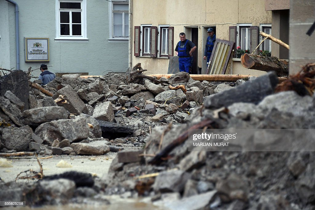 Two men look at rubble laying in a flooded street in Braunsbach, southern Germany, on May 30, 2016. Four people died and several more were injured in southern Germany after violent storms with torrential rains caused severe flooding, authorities said. / AFP / dpa / Marijan Murat / Germany OUT