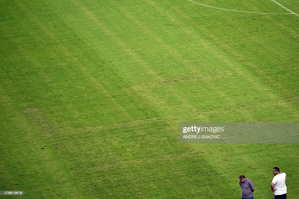 Two men look at the pitch appearing to show the pattern of a swastika following the the Euro 2016 qualifying football match between Croatia and Italy...