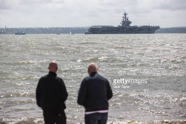 Two men look at US Navy Nimitzclass aircraft carrier USS George HW Bush anchored off the coast on July 27 2017 in Portsmouth England The 100000 ton...