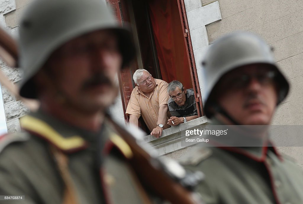 Two men look on as history reenactors dressed as World War I German soldiers parade past on May 27, 2016 in Verdun, France. The governments of France and Germany will commemorate the 100th anniversary of the World War I Battle of Verdun with ceremonies this coming Sunday. Approximately 300,000 soldiers lost their lives in the 10-month campaign that was among the most grueling battles of World War I.